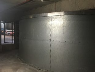 This Franklin Hodge sprinkler water tank in London was leaking from all the wall panel joints and bottom corner because the butyl rubber 'bag' liner was holed and letting the water behind it.